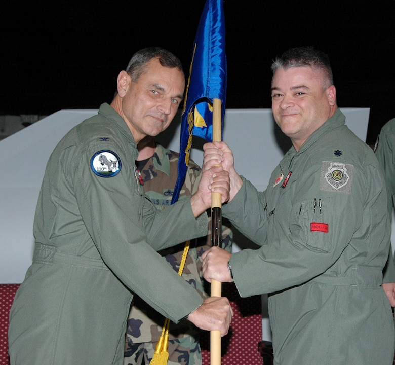 """Col. Robert Leeker, 131st Bomb Wing commander, presents the gideon to Lt. Col. Kenneth """"Willie B"""" Eaves, former 131st Fighter Wing chief of plans and programs and total force integration officer, to signify Colonel Eaves assumption of command of the 110th Bomb Squadron during a ceremony at Whiteman AFB Nov. 7.  Colonel Leeker explained, the assumption of command is the first for the 131st Bomb Wing at Whiteman AFB, first of many. (Photo by Master Sgt. Mary-Dale Amison)"""