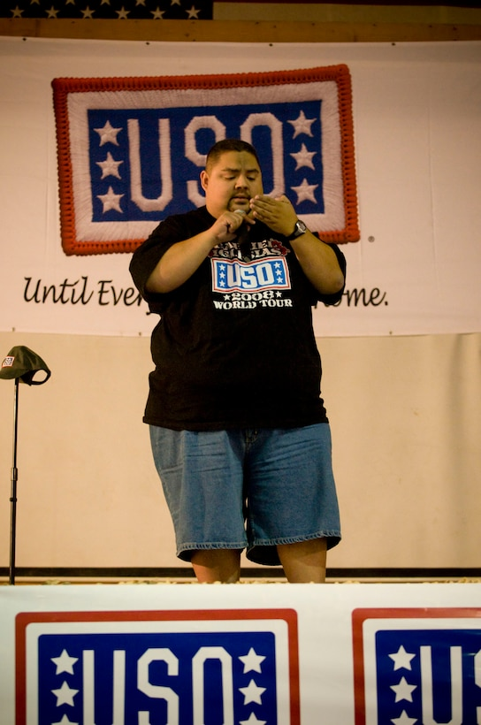 """Gabriel Iglesias, comedian with USO Tour """"Around the World in 8 Days,"""" pretends to use his iPhone while telling a story about text-messaging his wife after a night of drinking. Iglesias was one of four celebrities to perform for the troops at Bagram Air Field, Afghanistan, Nov. 13. (U.S. Air Force photo by Staff Sgt. Samuel Morse)(Released)"""