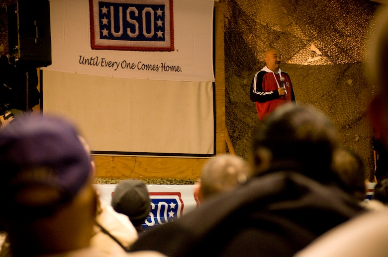 "Edwin San Juan, comedian and emcee for USO Tour ""Around the World in 8 Days,"" tells a joke to a joint-force crowd at Bagram Air Field, Afghanistan, Nov. 13. (U.S. Air Force photo by Staff Sgt. Samuel Morse)(Released)"