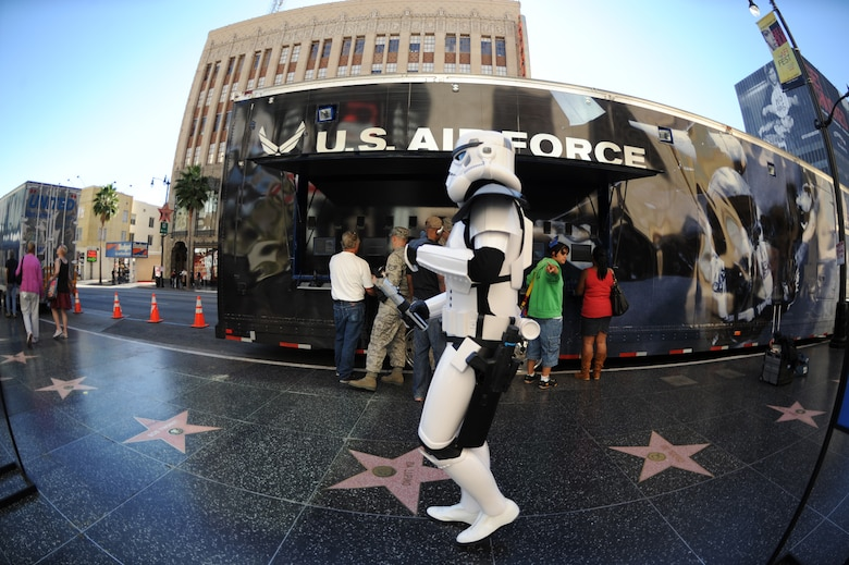 """A man dressed as a Star Wars Storm Trooper walks by as Los Angeles residents and tourists play a flight video game off the U.S. Air Force's 80-foot-long tour van called, """"Do Something Amazing,"""" during the Air Force Expo at Hollywood and Highland Boulevard in Los Angeles on Nov. 14. Air Force Week Los Angeles runs until Nov. 21 and has events throughout the area.  (U.S. Air Force photo/Staff Sgt. Desiree N. Palacios)"""
