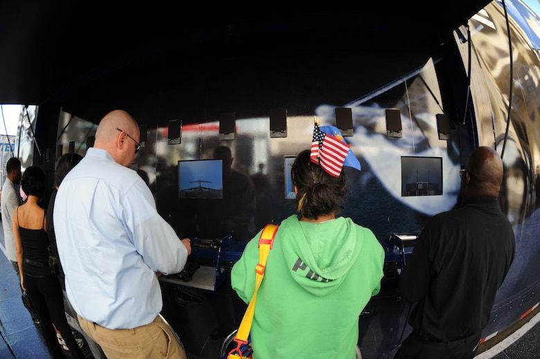 """Los Angeles residents and tourists play a flight video game off the U.S. Air Force's 80-foot-long tour van called, """"Do Something Amazing,"""" during the Air Force Expo at Hollywood and Highland Boulevard in Los Angeles on Nov. 14. Air Force Week Los Angeles runs until Nov. 21 and has events throughout the area.  (U.S. Air Force photo/Staff Sgt. Desiree N. Palacios)"""