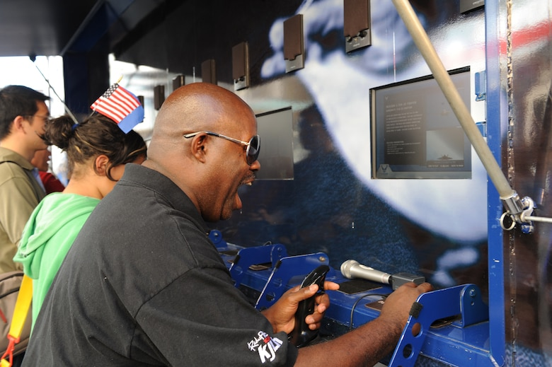 """Guy Black, from """"The Guy Black Show,"""" on 102.3 FM KJLH, a Los Angeles radio station, plays a flight video game off of the U.S. Air Force's 80-foot-long tour van, """"Do Something Amazing,"""" during the Air Force Expo at Hollywood and Highland Boulevard in Los Angeles on Nov. 14. The radio host saluted the men and women in uniform as he celebrated Air Force Week. Air Force Week Los Angeles runs until Nov. 21 and has events throughout the area.  (U.S. Air Force photo/Staff Sgt. Desiree N. Palacios)"""