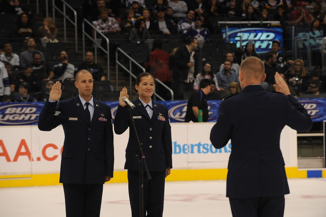 Col. John Odey swears in Tech. Sgt. Surita Rorie and Staff Sgt. Robert Coddington on the ice of the Staples Center, Los Angeles, Calif., Nov. 15. Sergeants Rorie and Coddington reenlisted during a Los Angeles Kings vs. Nashville Predator game as part of Air Force Week Los Angeles. Colonel Odey is the 95th Communications Group Commander, Edwards Air Force Base, Calif. Sergeants Rorie and Coddington are stationed at Edwards Air Force Base, Calif. Air Force Week Los Angeles is an event designed to educate the local population about the Air Force's capabilities and missions through various activities and exhibitions all over the Los Angeles area. It provides an up close and personal look at the men and women of the Air Force serving worldwide in the defense of freedom. Air Force Week Los Angeles runs from Nov. 14 to 21. (U.S. Air Force photo/Staff Sgt. Desiree N. Palacios)