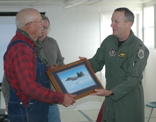 Reserve 419th Fighter Wing Commander, Col. Walter Sams, presents a photo of fighter aircraft operations on the Utah Test and Training Range to Mr. Cecil Garland, a resident of Callao, Utah, during the Moses Tour Nov. 6.  The outreach event is led by the 388th Range Squadron each fall to strengthen understanding of and support for the Air Force mission in communities underlying the UTTR. (U.S. Air Force photo)