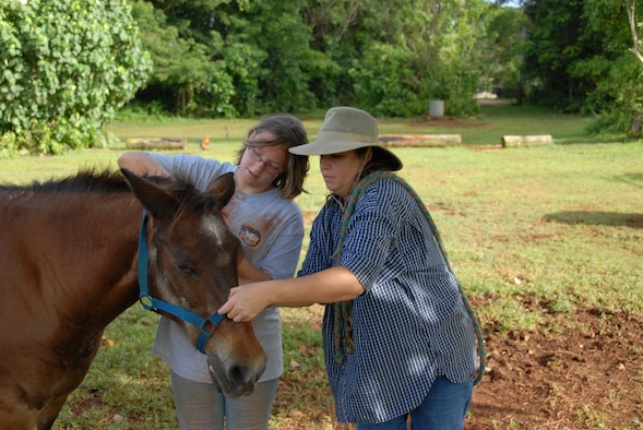 ANDERSEN AIR FORCE BASE, Guam - Deanna Tofte helps her daughter Shanna how a bridal a horse at the Horses of Sleepy Meadows Ranch in Yigo, Guam.  (U.S Air Force photo by Tech. Sgt. Brian Bahret)