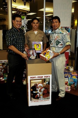 (From left to right) Geoff Loui, senior vice president of Strategy and Marketing, Lance Cpl. Isaac K. Yuen, Craig Inouye, senior vice president of sales display some toys that were collected by the Hawaiian Telcom employees Nov. 19 at the Pearlridge Shopping Center.  Hawaii Telcom has eight locations in Hawaii for people to drop off new, unwrapped toys to support the Toys for Tots program.