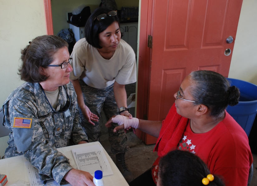 Army Maj. Nancy Gormley, a nurse from the JTF-Bravo Medical Element, and Air Force Staff Sgt. Kat Mansfield, an emergency medical technician, help a patient during a disaster relief medical mission Nov. 13 in Burrell Boom, Belize. More than 600 people were seen by U.S. and Belize military medical personnel in two different villages.