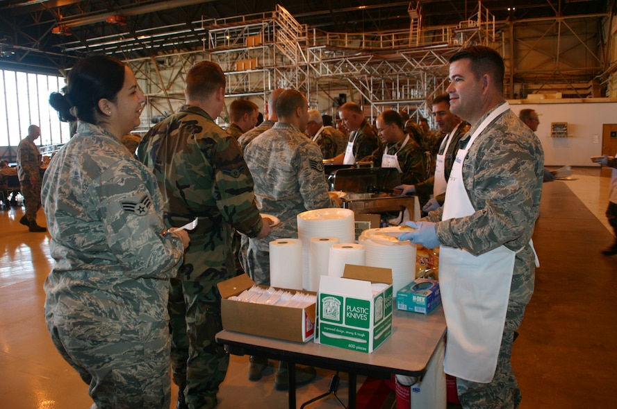 Maj. Dwight Minnick, commander, 552nd Maintenance Operations Squadron starts off the MXG Turkey Feast by handing out plates and bread rolls. Photo compliments of 1st Lt. Kinder Blacke.