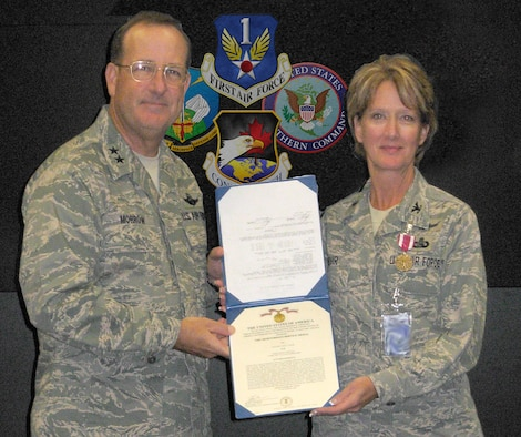 Maj. Gen. Hank Morrow, CONR-AFNORTH commander, presents Air Force Reserve Col. Jane Rohr with the Meritorious Service Medal for her contributions to the Joint Forces Air Component Commander. Graphic illustration by Master Sgt. Jerry D Harlan