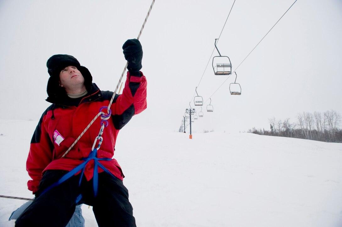ELMENDORF AIR FORCE BASE, Alaska -- Chaplain (Capt.) Kyle Roehrig, a volunteer for ski patrol, at lowers people from the ski lift at Hillberg ski hill Nov. 23. The ski patrols performed training on ski-lift evacuation prior to Hillberg's opening this week. (U.S. Air Force photo/Senior Airman Jonathan Steffen)