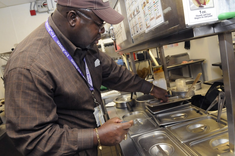Fred Brown checks the temperature on hot items to make sure they are 135 degrees or higher in the kitchen of Taco Johns in the BX food court Oct. 9. U. S. Air Force photo by Sue Sapp