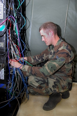 ANDERSEN AIR FORCE BASE, Guam - Airman 1st Class Joseph Lapthorne, 644th Combat Communications Squadron network control center operator, ensures local area connection cables are secure during the squadron's Dragon Thunder field training exercise Nov. 20 here. The field training exercise sharpened the 644th CBCS Airmen's expeditionary skills.