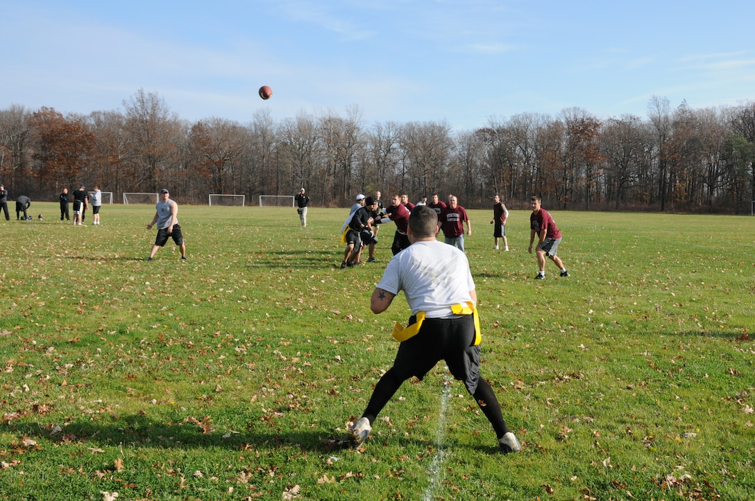Master Sgt. Jason Folckemer throttles the pig skin into the hands of Senior Airman Michael Badolato the play resulted in a touch down for the 107th Airlift Wing, Security Forces Squadron. The squadron spent their day at Fort Niagara State Park play in the Toys for Tots Flag Football Tournament. U.S. Air Force photo/Senior Airman Peter Dean