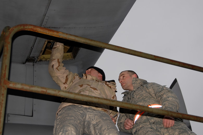 Airmen from the 133rd Airlift Wing work to install a part on a C-130 H3 in Canada. Technical Sgt. Corey Redder, 133rd Maintenance Squadron (left) helps Senior Airman Scott Mathiesen, also from the 133rd MXS, install a replacement valve on a C-130 H3 from the Minnesota Air National Guard. Redder and the crew arriving today in Canada are just returning from the combat zone, and they brought the needed part to the Minnesota C-130 crew on their way to Afghanistan.