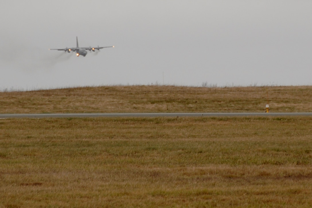 """A C-130 H3 """"Hercules"""" from the 133rd Airlift Wing of St. Paul, Minn. lands at a location in Canada, en route from Afghanistan and delivering a part to another C-130 from the Minn. Air National Guard. The second aircraft waits to fly on to Afghanistan."""