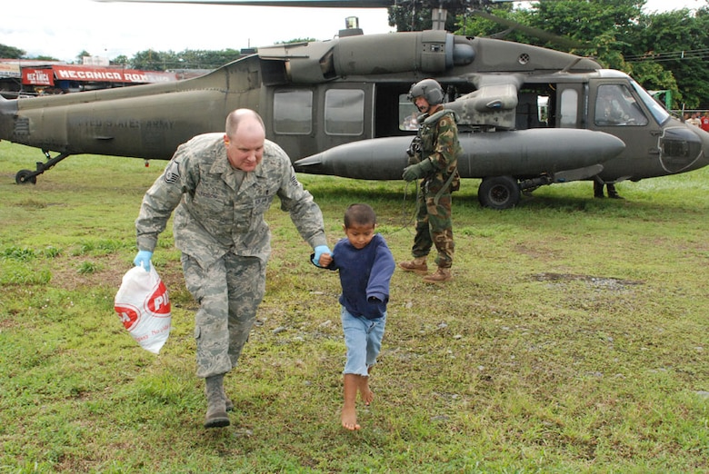 LAS TABLAS, PANAMA-- Master Sgt. James Eidson, a Joint Task Force-Bravo emergency medical technician, escorts a 6-year-old flood victim suffering from respiratory problems, from a UH-60 Black Hawk helicopter Wednesday. The helicopter transported six patients from Las Tablas to here where an ambulance was able to take them to a local hospital. The disaster response task force is here in response to a request from the Panamanian government for assistance with recent flooding caused by prolonged heavy rains in the country. (U.S. Air Force photo by 1st Lt. Candace Park)