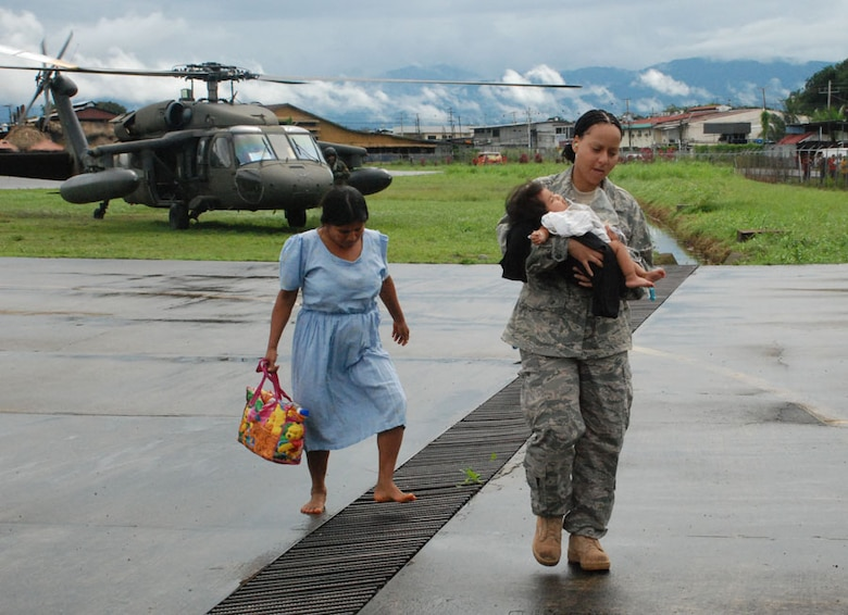 CHANGUINOLA, PANAMA-- Tech. Sgt. Tracy Fletcher, a Joint Task Force-Bravo emergency medical technician, carries a 7-month-old baby, suffering from severe dehydration, from a UH-60 Black Hawk helicopter to an ambulance awaiting to transport the baby to a local hospital. Eighteen service members from JTF-Bravo are here in support of a request from the Panamanian government for assistance with recent flooding caused by prolonged heavy rains in the country. (U.S. Air Force photo by 1st Lt. Candace Park)