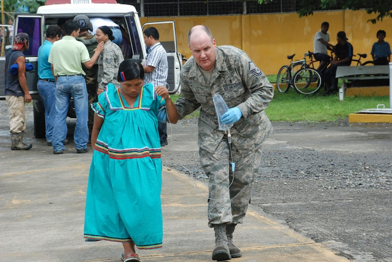 LAS TABLAS, PANAMA-- Master Sgt. James Eidson, a Joint Task Force-Bravo emergency medical technician, escorts a flood victim to a UH-60 Black Hawk helicopter Wednesday. The woman was unable to get to a hospital because the roads were flooded. The JTF-Bravo helicopter transported the woman and five other patients from a remote airfield to an airport where an ambulance met the patients and transported them to a local hospital. (U.S. Air Force photo by 1st Lt. Candace Park)