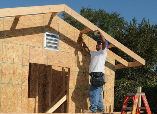 Mondo Rodriguez, a subcontractor for Pinnacle/Hunt, take a mesaurement on a carport being built in base housing Oct. 1. (U.S. Air Force photo by Rich McFadden)