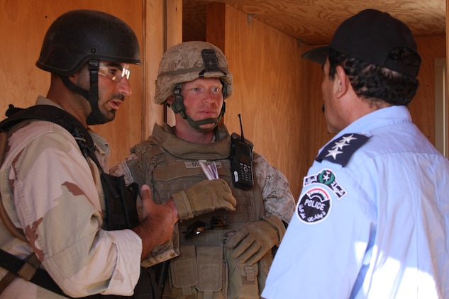Capt. Ty Moore, the commanding officer for Company A, 1st Battalion, 7th Marine Regiment, talks to an role player acting as an Iraqi policeman with the aid of a translator during a battalion clear of the Combat Center's military operations in urban terrain facility at range 215 Oct. 2. Company A found every IED threat, did not injure or kill any civilians, worked well with the Iraqi Police, and even impressed the role players. At the debriefing immediately following the exercise, a role player addressed the company and told the Marines personally that their effort was the best he had seen because it was accurate and the civilian population and homes of the mock-village were respected.