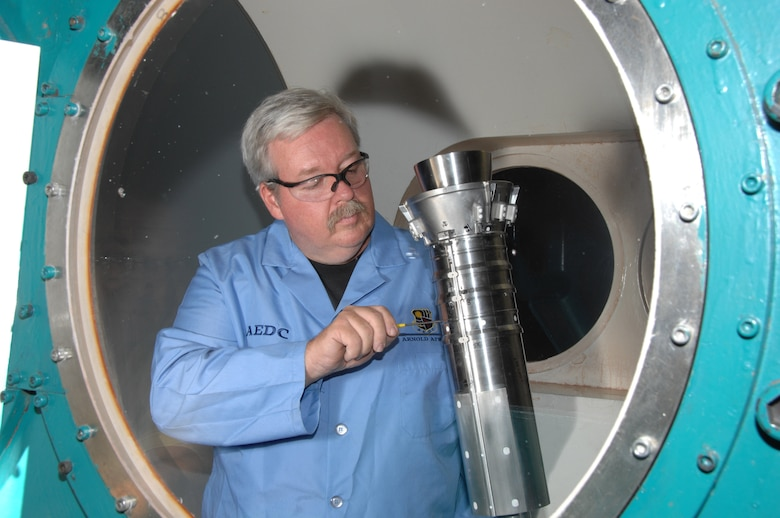 Joe Syler, Aerospace Testing Alliance outside machinist, makes an adjustment to the Ares I first stage booster model in the center's von Karman Facility's Tunnel B prior to the resumption of heat transfer testing. (Photo by David Housch)