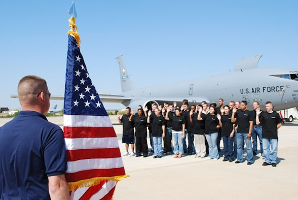 As an Air Force Reserve recruiter holds the American flag, 25 young citizens take the oath of enlistment during a mass enlistment ceremony in front of a KC-135R here at Tinker Air Force Base October 5.  These new recruits will be assigned to either the Air Force Reserve Command's 507th Air Refueling Wing or 513th Air Control Group upon graduation from basic training and technical school.