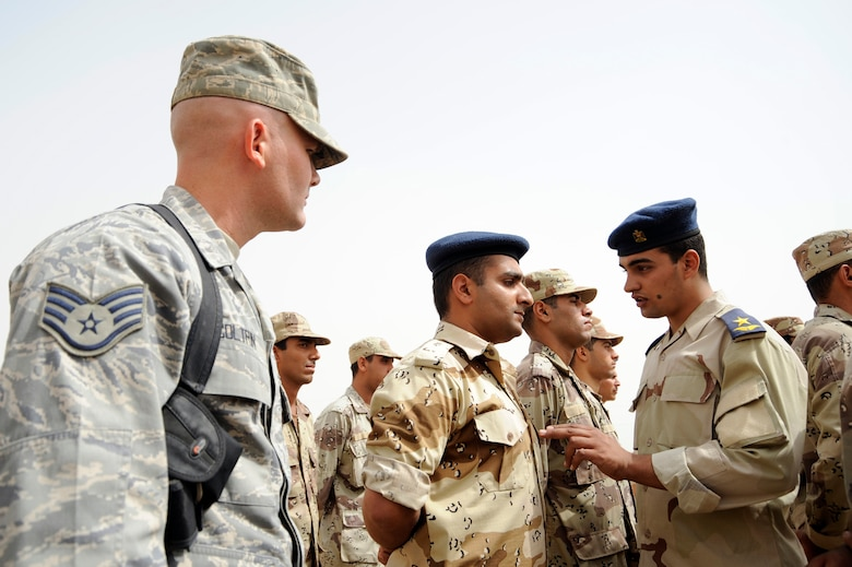 AL TAJI AIR BASE, Iraq -- U.S. Air Force Staff Sgt. Matthew Coltrin, left, a military training instructor air advisor, 370th Expeditionary Training Squadron, watches Iraqi air force Lt. Ali, right, military training instructor, explain the importance of military bearing to a warrant officer during parade practice. (U.S. Air Force photo/Staff Sgt. Paul Villanueva II)