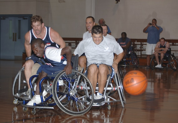 Maj. Lance Rosa-Miranda, 1st Special Operations Wing executive officer, chases a loose ball at the annual wheelchair basketball game Oct. 2 at the Fort Walton Beach Community Center. The competition, pittting Airmen from Hurlburt Field against the Mobile Patriots, a professional wheelchair basketball team, is held in recognition of National Disability Awareness Month. Despite spotting the Commandos 40 points, the Patriots won the game 58-46. (U.S. Air Force photo/ Senior Airman Emily Moore)