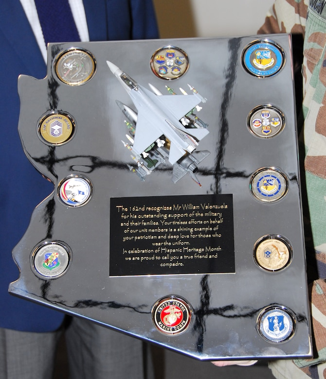 """Staff Sgt. Robert Pensas, Master Sgt. Miguel Islas, and Senior Airman Ben Koughn present a chromed plaque they constructed by hand to Mr. William Valenzuela. Using skills and knowledge gained from working in the wing's metals shop, the Guardsmen constructed this memento in the shape of the state and included challenge coins from various units on base. """"I used to be a machinist so this means more to me than you know,"""" said Valenzuela. (Air National Guard photo by Master Sgt. Dave Neve)"""