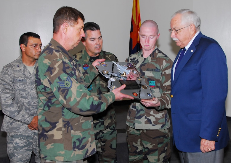 """(From left to right) Col. Jose Salinas, vice wing commander, looks on while Staff Sgt. Robert Pensas, Master Sgt. Miguel Islas, and Senior Airman Ben Koughn present Mr. William Valenzuela a chromed plaque they constructed by hand. The plaque reads, """"The 162nd recognizes Mr. William Valenzuela for his outstanding support of the military and their families. Your tireless efforts on behalf of our unit are a shining example of your patriotism and deep love for those who wear the uniform. In celebration of Hispanic Heritage Month we are proud to call you a true friend and compadre."""" (Air National Guard photo by Master Sgt. Dave Neve)"""