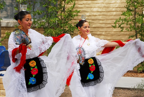 Rachel Gomez (left) and Jacqui DuPont, from Tucson's Ballet Folklorico Los Mextucaz, demonstrate Mexican folk dancing in the 162nd Fighter Wing Minuteman Courtyard, Oct. 3. (Air National Guard photo by Master Sgt. Dave Neve)