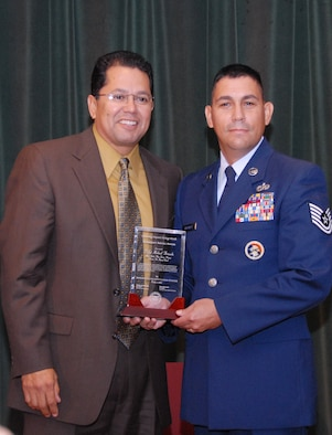 Arizona Sen. Richard Miranda presents a Latino Caucus Award to Tech. Sgt. Michael Brizuela at a ceremony in Phoenix, Oct. 1. Sergeant Brizuela was recognized for his community involvement and leadership. He is an F-16 crew chief at the 195th Fighter Squadron in Tucson, Ariz. (Air National Guard photo by Master Sgt. Charles Wade)