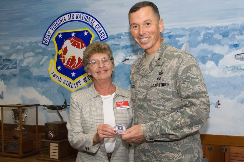 Mrs. Sandy Chrisman, 167th Airlift Wing Shoppette Manager, is presented with Brig. General Fran L. Hendricks' Coin of Excellence. Gen. Hendricks is the Deputy Commanding General for the Army and Air Force Exchange Service (AAFES). His primary reason for visiting the 167th Airlift Wing on Sept. 26 was to ensure that AAFES was providing positive customer service to the Wing and to recognize Mrs. Chrisman for her outstanding performance.