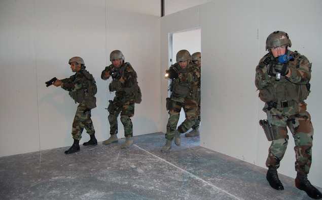 Members of the 341st Security Forces Group Tactical Response Force team make their way through the new close-quarters battle center and clear the scene Sept. 30 during a training scenario. The training facility was a self-help project planned and constructed by 341st SFG personnel who volunteered hundreds of hours of their time to build the center.  Team members include (left to right) Senior Airman Liseth Rodriguez, Staff Sgts. David Barger and Derik Morris, and Senior Airman Samuel Fullerton.  (U.S. Air Force photo/Senior Airman Eydie Sakura)