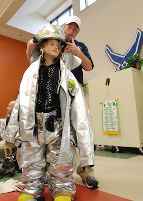 Airman 1st Class William Pritchett, 22nd Air Refueling Wing fireman, dresses Emilee Patten, daughter Tech Sgt. Shawn Patten and wife, Corina, in bunker gear (fire suit) during Fire Prevention Week at the McConnell School Age Program, Oct 6. (Photo by Airman 1st Class Jessica Lockoski)
