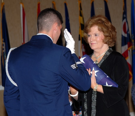 Martha Rodgers, 14th Flying Training Wing Installation Deployment Officer, is presented a flag in honor of her 39 years of federal service by honor Guard member Senior Airmen Matthew Terkay at her retirement  ceremony on Oct. 3. (U.S. Air Force photo)