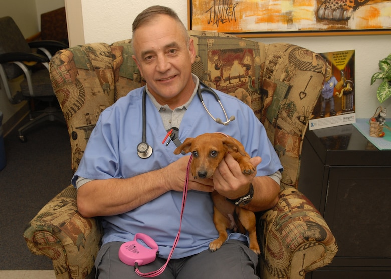 Army Capt. Tom Mason, 20th Special Forces Group, Army National Guard, takes a moment to pose with his patient Savannah during her recent visit to the Goodfellow Air Force Base veterinary clinic Oct. 1. The Goodfellow vet clinic is open for appointments from 9 a.m. - 3 p.m. Tuesdays. (U.S. Air Force photo by Senior Airman Kasabyan Musal)