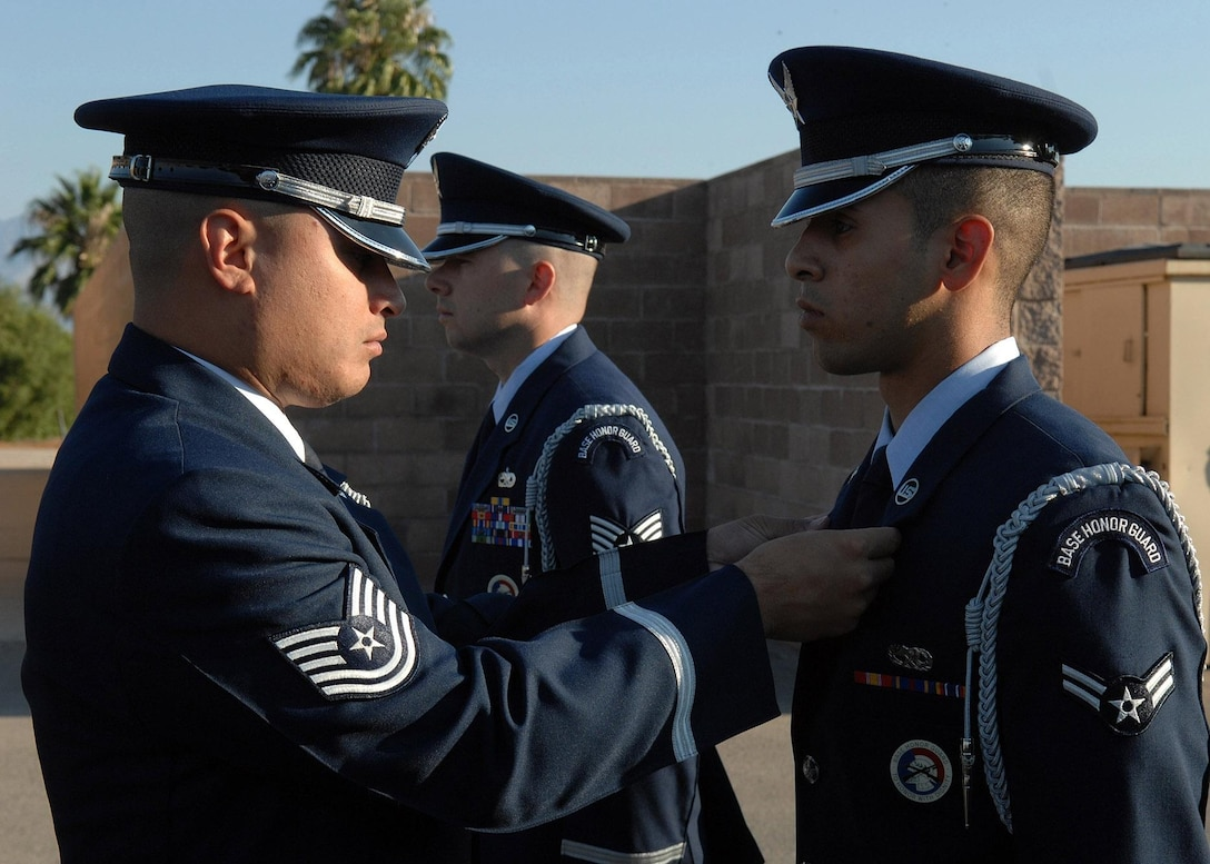 Tech Sgt. Jason Estrada, U.S. Air Force Honor Guard noncommissioned officer in charge of the Base Honor Guard Training Program, inspects  a base honor guardsman's dress uniform during a training visit to Davis-Monthan Air Force Base, Ariz. (Photo courtesy of U.S. Air Force Honor Guard)
