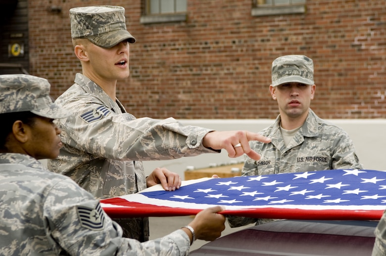 Staff Sgt. Alex Frizzo, U.S. Air Force Honor Guard formal training instructor, advises base honor guardsmen on proper flag-folding techniques during a reent training visit to McChord Air Force Base, Washington. (Photo courtesy of U.S. Air Force Honor Guard)