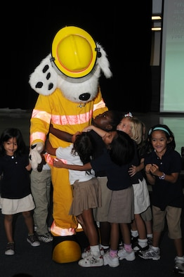 "ANDERSEN AIR FORCE BASE, Guam - Airman Colton Balthazor, 36th Civil Engineer Squadron firefighter, receives smiles and big hugs from Andersen's Elementary School students during Fire Prevention Week here Oct. 9. The character ""Scruffy"" is used to entertain and inform children on the importance of fire safety. (U.S. Air Force photo by Senior Airman Sonya Croston)"