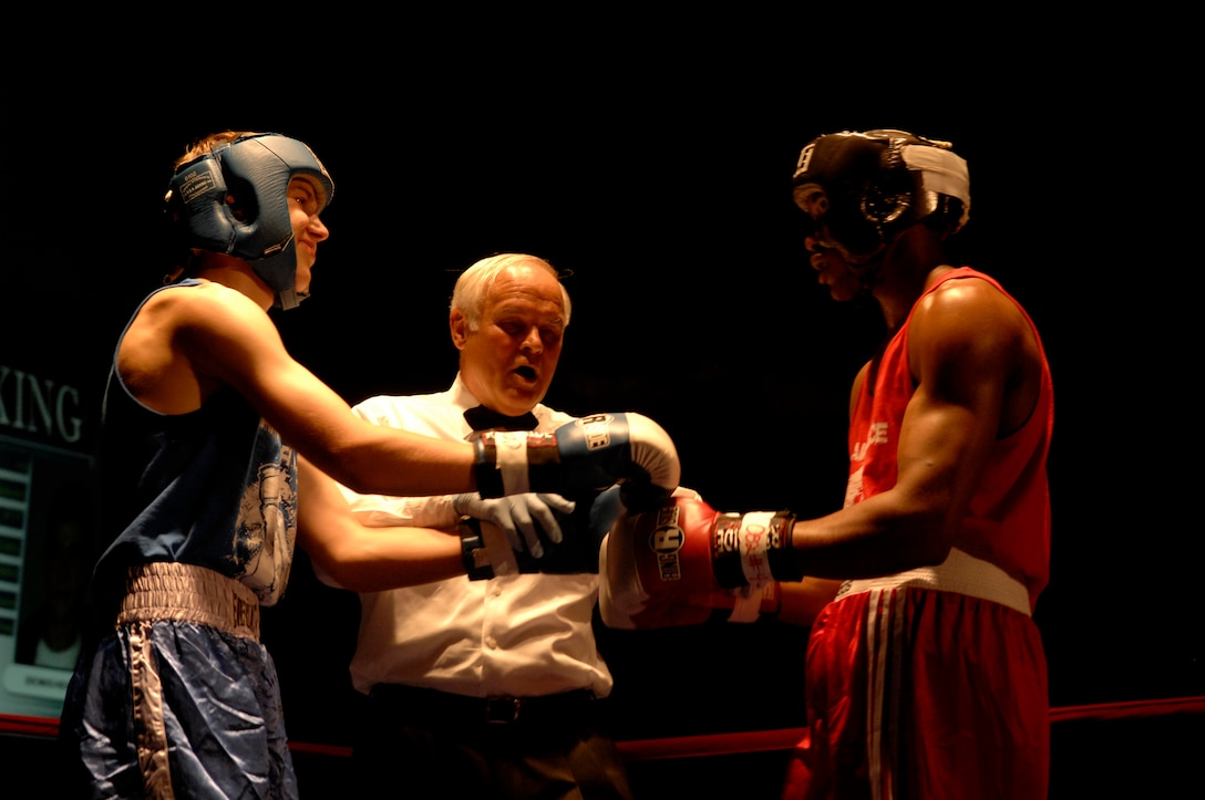 United States Air Force Staff Sgt. Harold Davis (red trunks), 86th Maintenance Squadron, Ramstein Air Base, and Denis Heier (blue trunks), a German boxer from the Turngemeinde Boxing Club, listens to Referee Tom Hlavacek  prior to a boxing match, Vogelweh Air Base, Germany, Oct. 11, 2008. Staff Sgt. Davis lost his match against Heier. (U.S. Air Force photo by Senior Airman Amber Bressler)(Released)