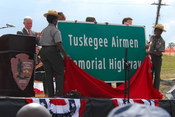As part of the opening ceremony of the Tuskegee Airmen National Historic Site Oct. 10 at Moton Field, Ala., National Park Service officials unveil a sign that designates part of Interstate 85, which passes near the city of Tuskegee, as the Tuskegee Airmen Memorial Highway. Sen. Jeff Sessions of Alabama looks on from behind. (Air Force photo by Scott Knuteson)