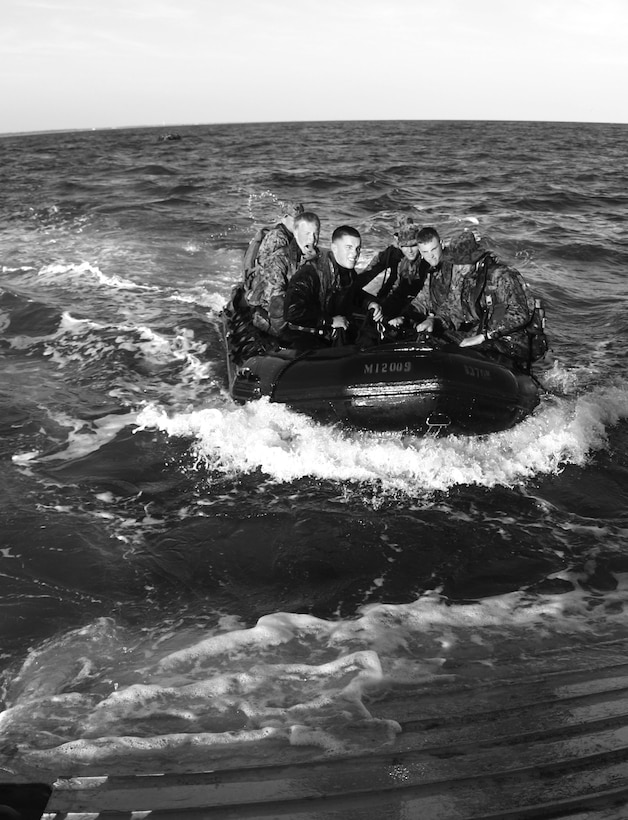 Force Reconnaissance Marines approach a beachhead in a zodiac, a small rubber craft designed to transport up to eight men.