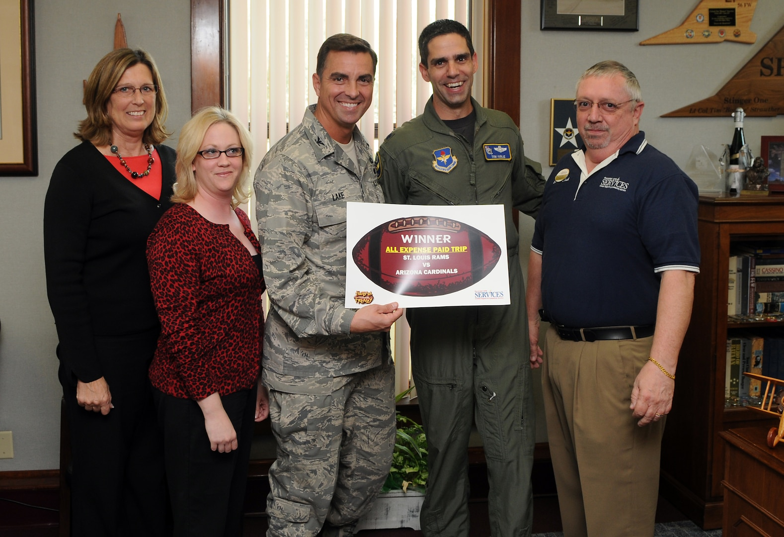 Col. Alan Lake (left), 12th Mission Support Group commander, surprises Lt. Col. Tom Kublie, 19th Air Force Undergraduate Training Branch chief, on Oct. 21 with an all-expense paid trip for two to watch the Arizona Cardinals play the St. Louis Rams on Dec. 7. Colonel Kublie entered the Football Frenzy competition held by the Air Force Services Agency and was selected as the regular season game package winner. The grand prize, which includes an all-expense paid trip for two to Super Bowl XLIII in Tampa Bay, Fla., will be held in early January. Services Club members who attend a Football Frenzy celebration at the enlisted or officers' club can enter by filling out a form, with no purchase neccessary. (U.S. Air Force photo by Rich McFadden)