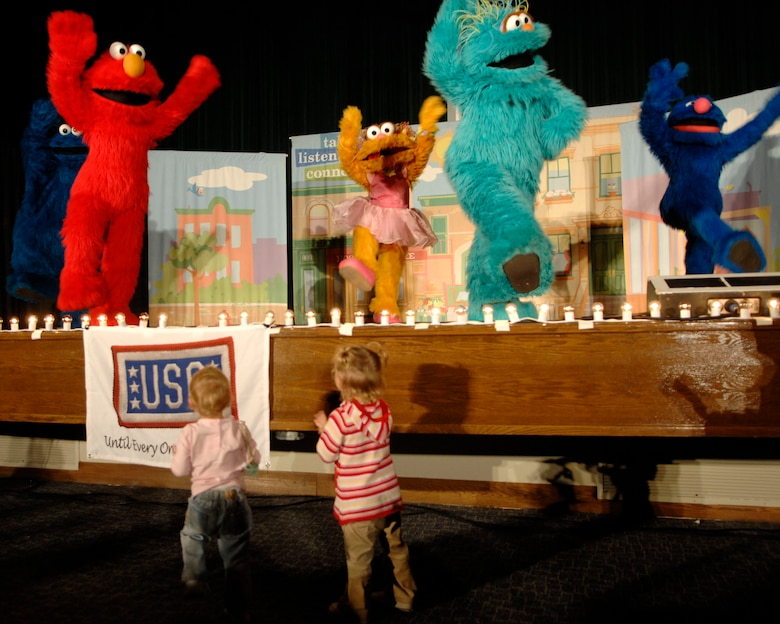 """Cookie Monster, Elmo, Zoe, Rosita, and Grover sing and dance to several of their hits such as """"Somebody Come and Play,"""" and the """"Sesame Street"""" theme song during """"The Sesame Street Experience for Military Families"""" USO Tour Oct. 16 and 17 at the base theater. Military families who attended the show received giveaways and outreach materials from Talk, Listen, Connect and other partners that sponsored this free event. (U.S. Air Force photo/Senior Airman Steven R. Doty)"""