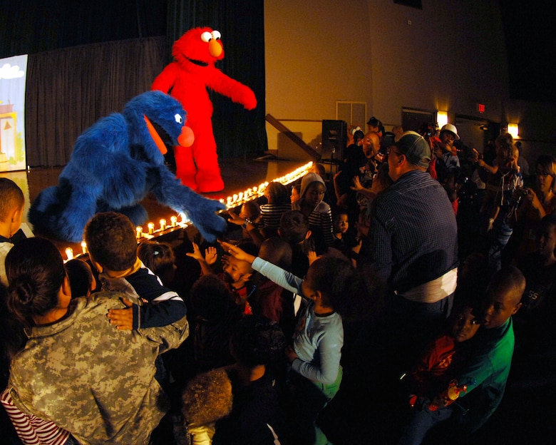 """Grover and Elmo take time to meet children during """"The Sesame Street Experience for Military Families"""" USO Tour Oct. 16 and 17 at the base theater. The show was designed to provide parents with new tools to help their children learn how to deal with the hardships of deployments and military life. (U.S. Air Force photo/Senior Airman Steven R. Doty)"""