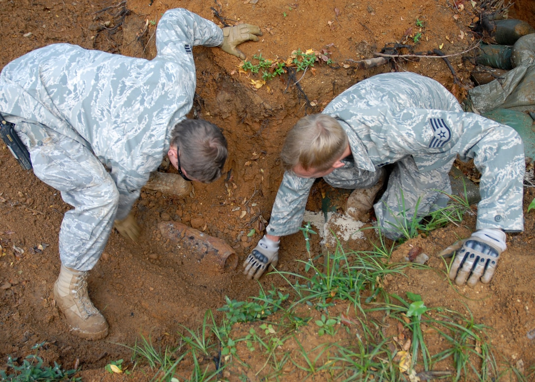 Senior Airman Tristan Persico (left) and Staff Sgt. Jason Weimer (right), 18th Civil Engineer Squadron Explosive Ordnance Disposal specialists, brush away dirt from a UXO at Kadena Air Base, Japan Oct. 19, 2008.  The 18th Wing partnered with local government agencies to successfully remove the UXO while ensuring the safety of local citizens. EOD specialists safely destroyed the munition on the EOD range in the Kadena Munitions Storage Area. The 35-pound World War II-era rocket warheard was discovered near the base fence line during construction activities on Aug. 6. (U.S. Air Force photo/Airman 1st Class Amanda Grabiec)