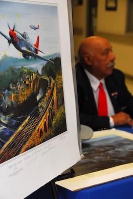 Retired Lt. Col. William Holloman, one of the original Tuskegee Airmen, signs autographs near a lithograph depicting the Tuskegee Airmen in combat during World War II. (Air Force photo by Scoot Knuteson)