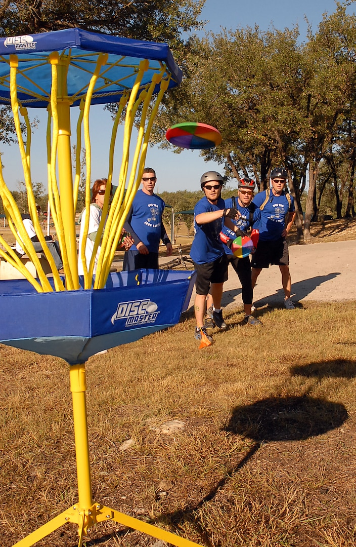 Brian Broyles, James Sayres, Michael Humphrey and Tim Okkerse, ?Texas Port Dawgs? relay team, make a toss for the disc golf portion of the Rambler 120. Participants from four U.S. Air Force Bases competed in the triathlon held each year at Canyon Lake. (U.S. Air Force photo by Staff Sgt. Tim Bazar)