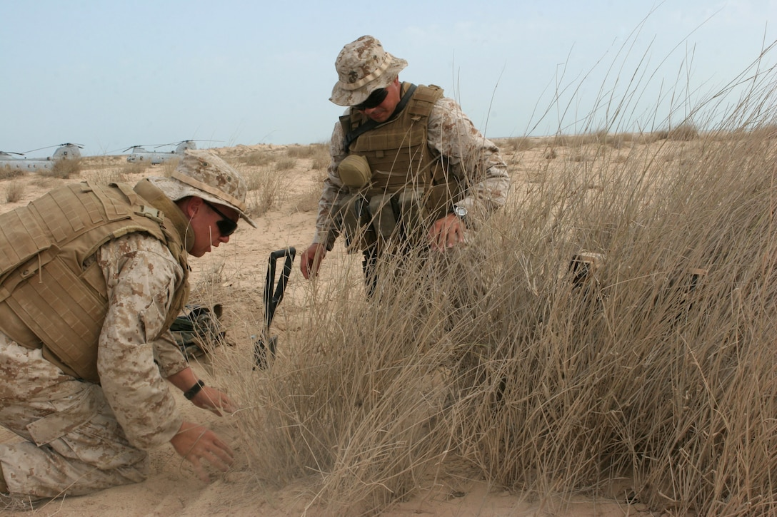 Lance Cpls, Barry L. Saucer and Jaime J. Sweeney, Marines from Ground Sensor Platoon, 26th Marine Expeditionary Unit, practice camouflaging an emplaced surveillance instrument, Oct. 24, 2008, in the Middle East.  The 26th MEU was conducting bilateral training exercises with the host nation.